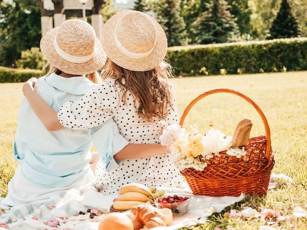 トレンディな夏のサンドレスと帽子の2人の若い美しい笑顔のヒップスターの女の子の背面図。外でピクニックをする女性。