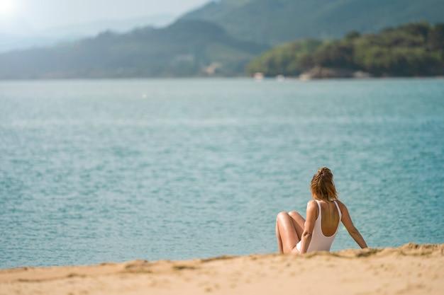 Вид сзади неизвестной женщины, загорающей на пляже против моря. на ней белые купальники. она одна.