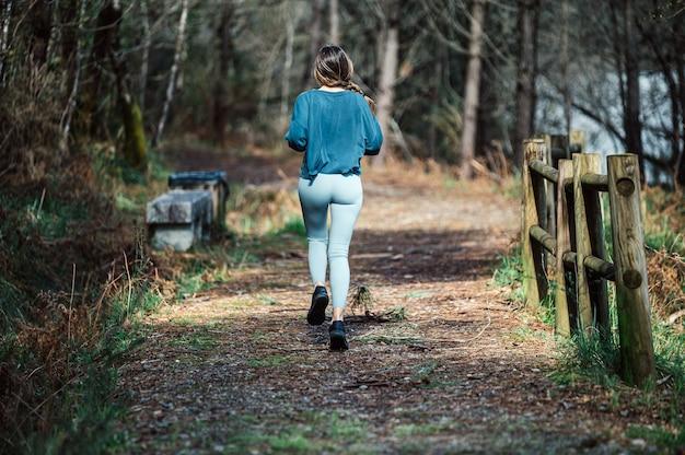 녹색 숲의 흔적을 따라 달리는 activewear에서 인식 할 수없는 맞는 여성의 뒷모습