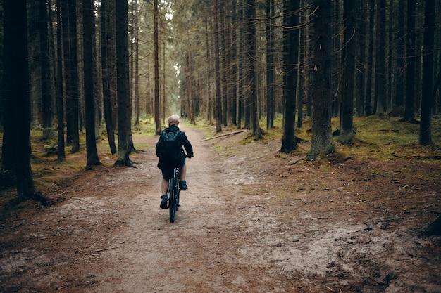 숲에서 버려진 길을 따라 마운틴 자전거를 타고 인식 할 수없는 남자의 다시보기. 주위에 아무도와 평화로운 아침에 숲에서 남성 자전거의 후면 샷. 사람, 자연 및 스포츠 개념