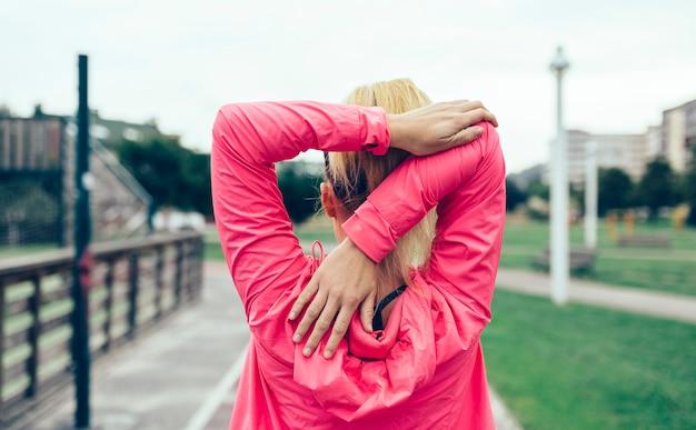 야외에서 훈련하기 전에 팔을 쭉 뻗고 있는 분홍색 운동복을 입은 알아볼 수 없는 여성의 뒷모습