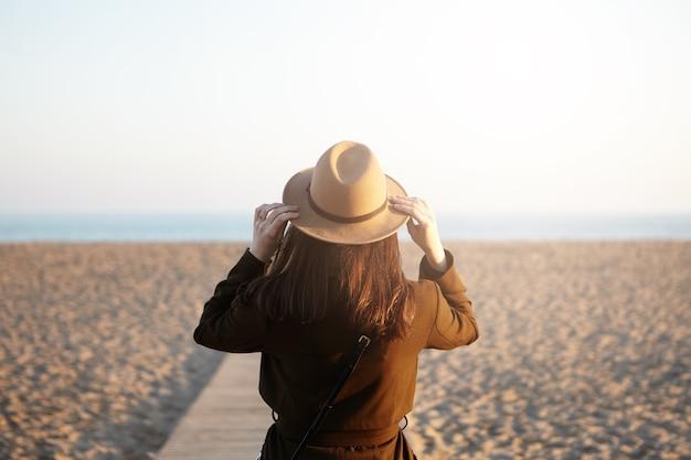 服に身を包んだ認識できない若いブルネットの女性の背面図
