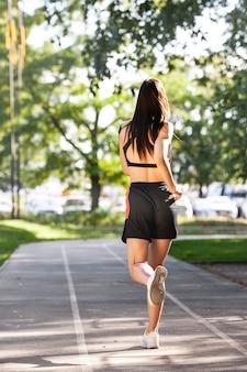 Вид сзади неузнаваемого молодого кавказского профессионального женского бегуна с эластичными кинезиологическими лентами на теле, бегущем на стадионе.