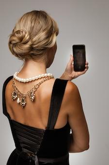 Вид сзади неузнаваемой молодой женщины со светлыми волосами в прическе в черном бархатном платье и ожерельях на спине. женщина, принимающая селфи, держащая мобильный телефон.