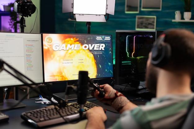 스트리밍 채팅이 열린 상태에서 전문 설정을 사용하여 게임 경쟁을 하는 화가 난 스트리머의 뒷모습. 무선 컨트롤러와 전문 헤드폰을 사용하여 게임 의자에 앉아 있는 게이머