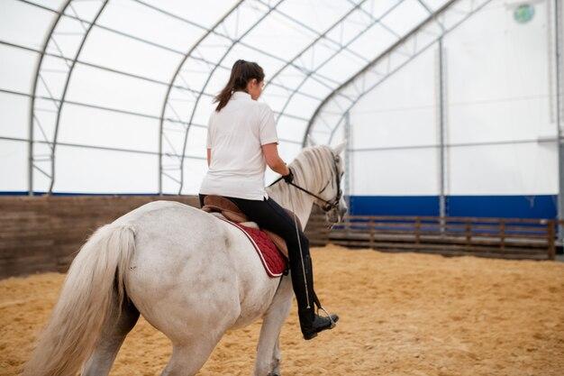 경주 전에 훈련하는 동안 모래 경기장 아래로 이동하는 뒷면에 젊은 활성 여자와 흰색 경주마의 다시보기