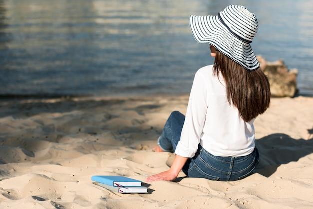 ビーチからの眺めを眺める女性の背面図