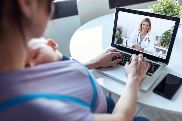 집에서 노트북 전문가와 온라인으로 의료 상담을 하는 여성과 그녀의 아기 아들의 뒷모습.