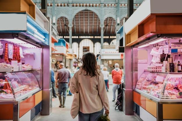 Вид сзади женщины на рынке