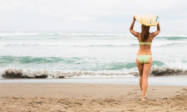 Вид сзади женщины, несущей доску для серфинга на пляже