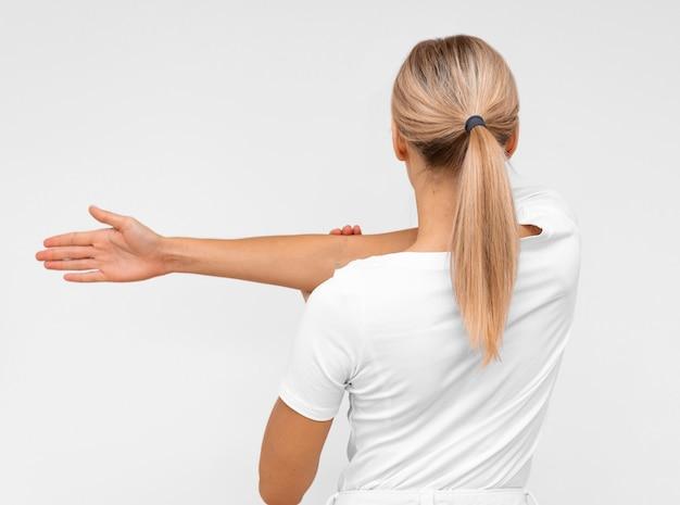 Вид сзади женщины, делающей лечебную физкультуру
