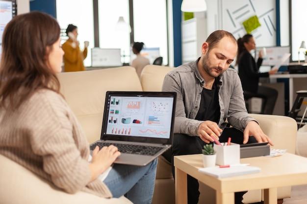 동료들이 백그라운드에서 일하는 동안 노트북 컴퓨터를 사용하여 사무실에서 소파에 앉아 있는 여성 기업가의 뒷모습