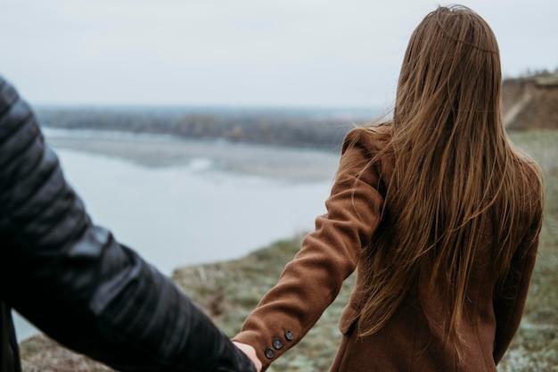 彼女のボーイフレンドの手を握っている女性の背面図