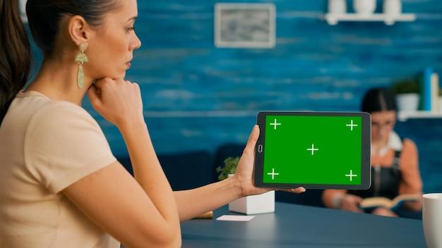 녹색 화면 크로마 키 디스플레이가 있는 태블릿 컴퓨터를 들고 있는 여성의 뒷모습. 홈 오피스 스튜디오에 앉아 온라인 브라우징을 위해 터치스크린 장치를 사용하는 백인 여성
