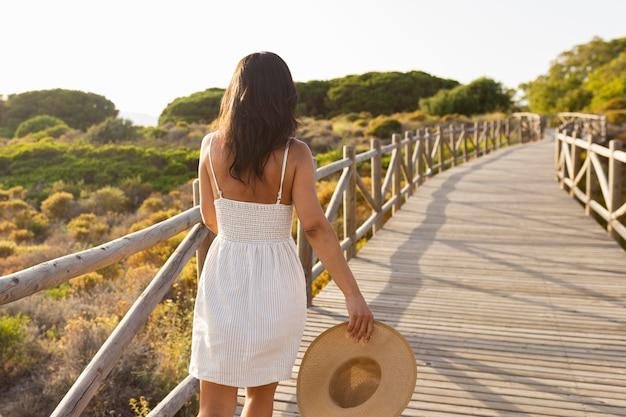 Вид сзади женщины в природе с шляпой