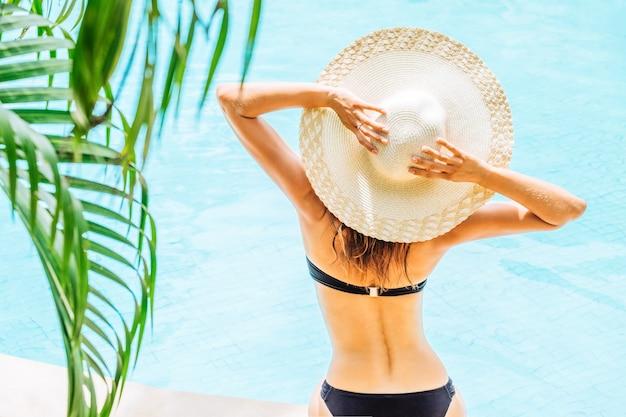 Вид сзади женщины в купальнике и шляпе возле бассейна