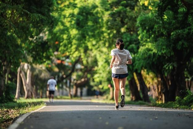 公園でジョギングや屋外で運動している女性の背面図、健康的なライフスタイルの概念。