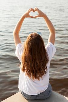 湖のほとりに愛のサインを作る女性の背面図