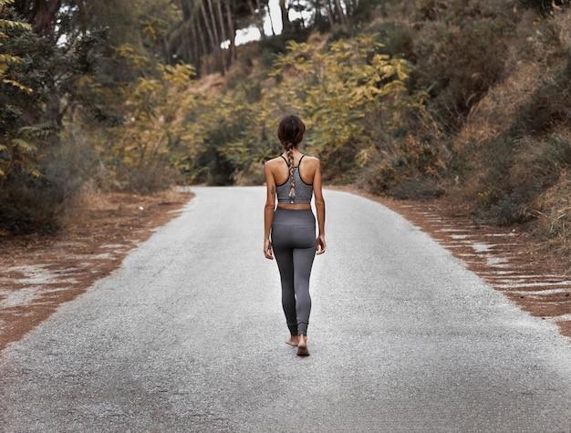 Вид сзади женщины на дороге, занимающейся йогой