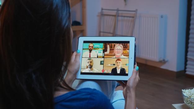 快適なソファに座っているビデオ通話の女性の背面図。インターネット技術を使用したビデオ会議やウェブカメラチャットで同僚とオンライン会議のコンサルティングを行っているリモートワーカー。