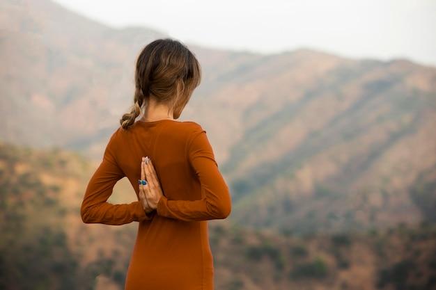 Вид сзади женщины на открытом воздухе на природе в позе йоги с копией пространства