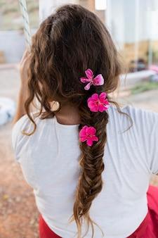 屋外の髪に花とスイングの女性の背面図