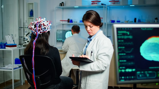 Вид сзади пациентки, носящей эффективную гарнитуру для сканирования мозговых волн, сидящей в медицинской неврологической лаборатории, пока исследователь настраивает ее, исследует нервную систему, печатая на планшете