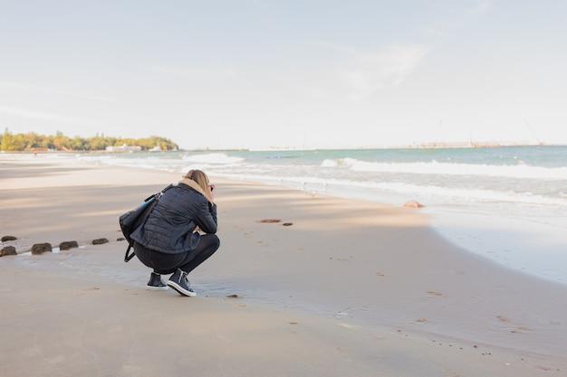 Вид сзади женщина, фотографируя море с камерой или смартфоном, стоя на фоне копией пространства моря и неба