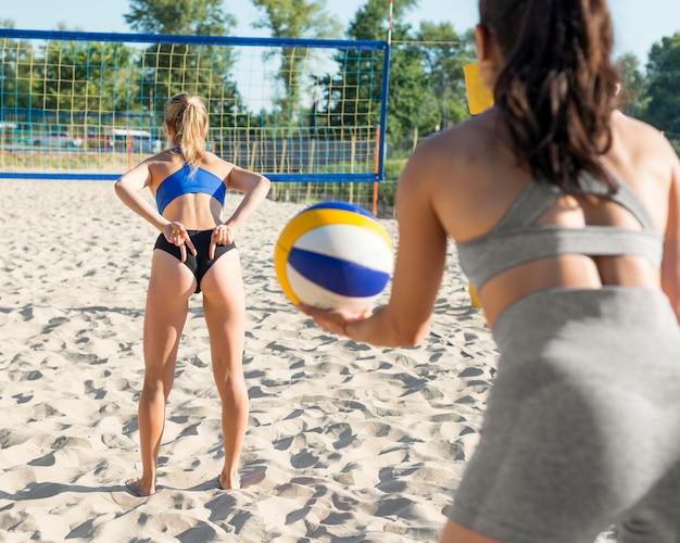 後ろのチームメイトに手信号をやっているバレーボールを再生する女性の背面図