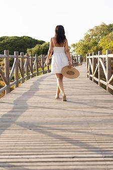 Вид сзади женщина позирует на мосту в природе