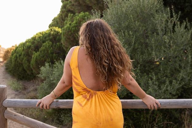 木製のフェンスに触れながらポーズの女性の背面図