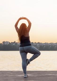 日没時にヨガを練習している女性の背面図