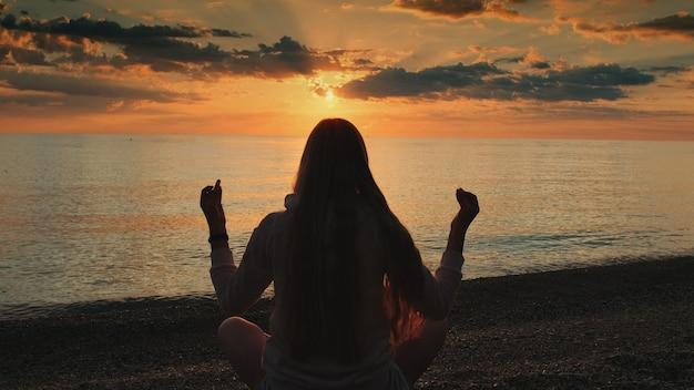 Вид сзади женщины, практикующей йогу в позе медитации на пляже
