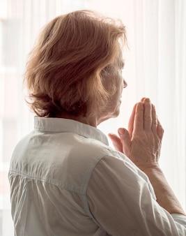 祈る女性の背面図