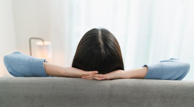 自宅で仕事をした後、快適に休んでソファでリラックスしている女性の背面図。