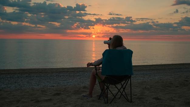 キャンプチェアに座って、コーヒーを飲む女性の背面図。リラックスして自然を楽しんでください。海の日の出を眺める。