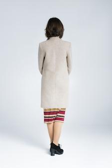 Вид сзади женщины, стоящей изолированной на белом фоне