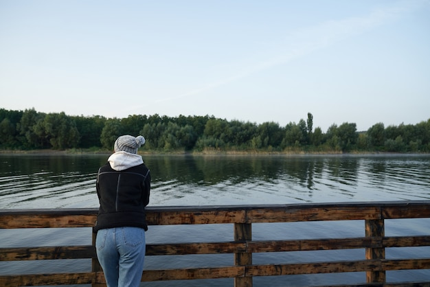 Вид сзади женщины, стоящей на пирсе возле озера
