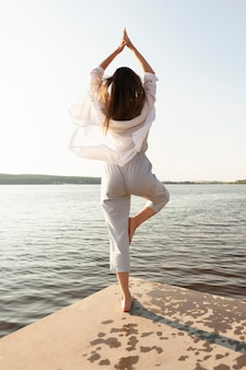 湖のほとりでポーズを打つ女性の背面図