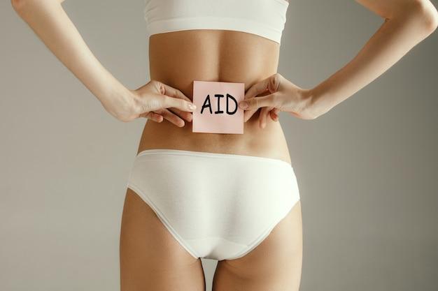 灰色の壁に分離された単語aidを取る女性の背面図