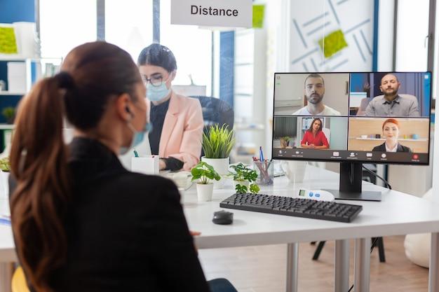 코로나바이러스로 인한 세계적 대유행 시기에 새로운 일반 사무실에서 원격 화상 회의 중에 팀과 이야기하는 여성의 뒷모습, 얼굴 마스크를 쓰고 사회적 거리를 유지합니다.