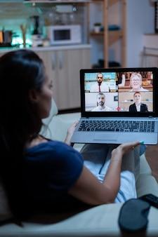 快適なソファに座ってビデオ通話でラップトップを使用している女性の背面図。インターネット技術を使用したビデオ会議やウェブカメラチャットで同僚とオンライン会議のコンサルティングを行っているリモートワーカー。