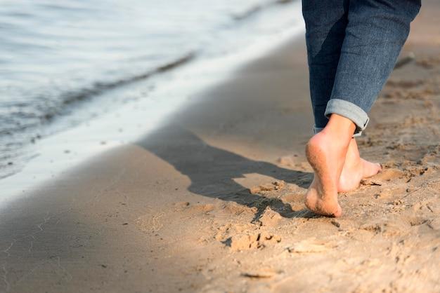 Вид сзади женщины, идущей босиком на пляже