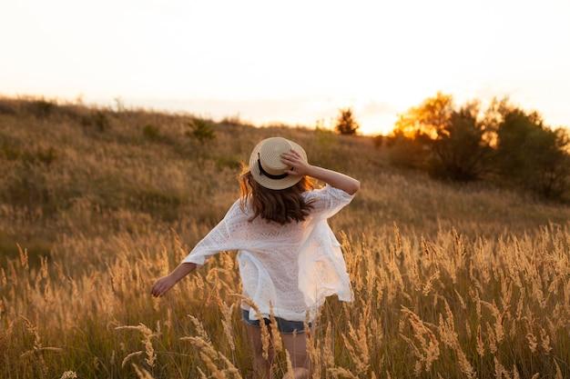 Вид сзади женщины в шляпе и позирует в полях