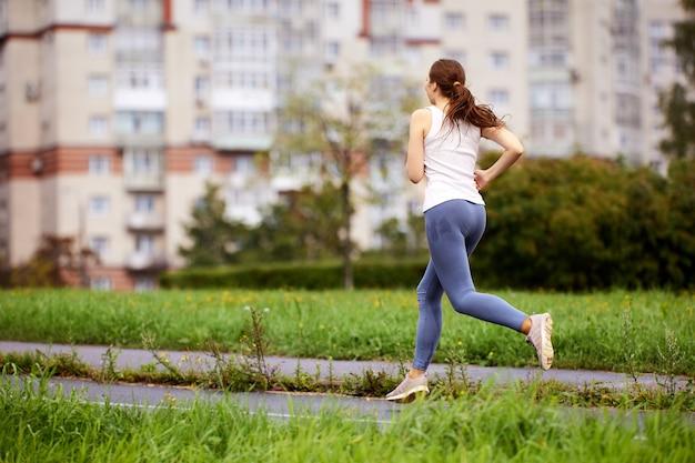 Вид сзади женщины, которая работает в парке в дневное время