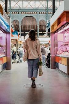 市場で食料品の袋を持つ女性の背面図