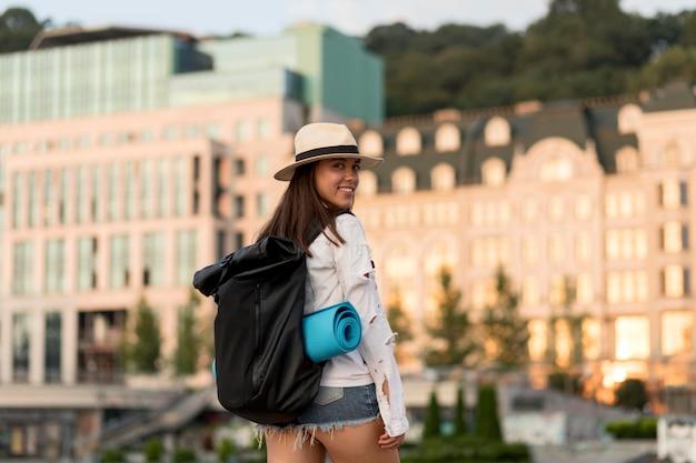 旅行中にバックパックを運ぶ帽子の女の背面図