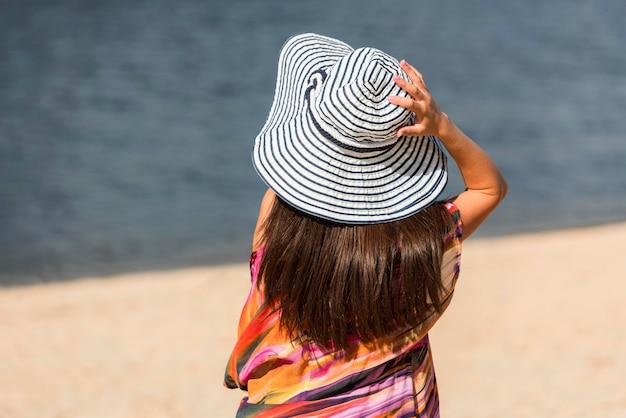 ビーチで帽子をかぶった女性の背面図