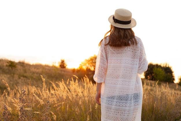 屋外のフィールドでポーズをとって帽子をかぶった女性の背面図
