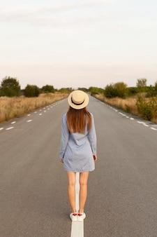道路の真ん中でポーズをとって帽子をかぶった女性の背面図